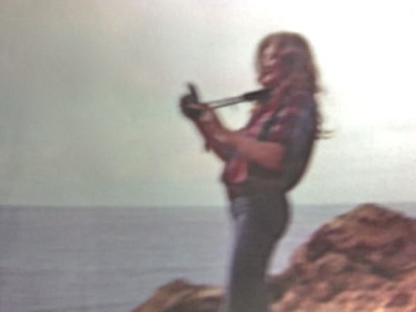 TRISH WILCOX in a rare shot with her guitar on the beach in Malibu