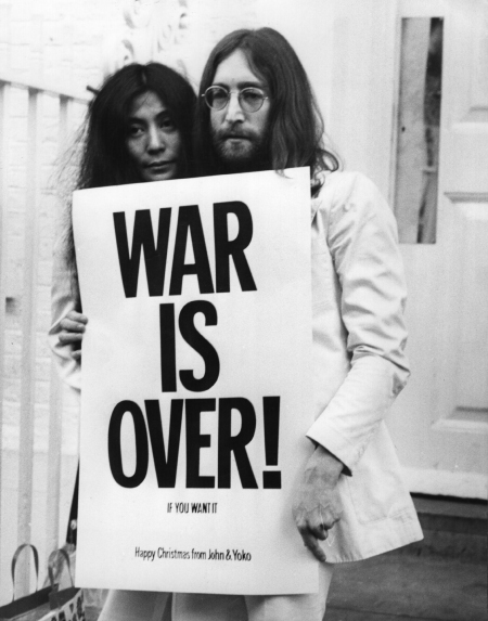John Lennon and Yoko Ono with sign saying WAR IS OVER IF YOU WANT IT and HAPPY CHRISTMAS FROM JOHN & YOKO